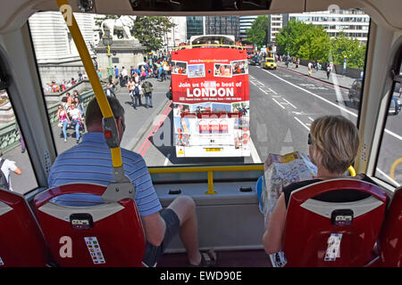 Tourist holds map sitting front seats on top deck of tour bus crossing River Thames on Westminster Bridge more tour - Stock Photo