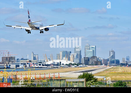 British Airways airplane landing London City Airport Newham with O2 arena & Canary Wharf in London Docklands skyline - Stock Photo