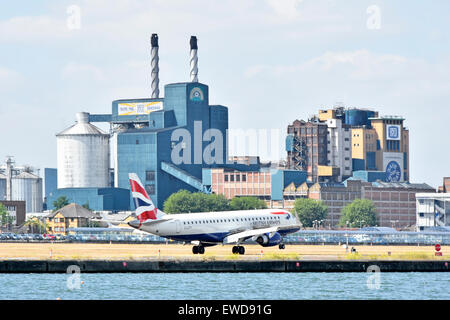 British Airways flight landing at London City Airport with Tate and Lyle Silvertown sugar refinery factory buildings - Stock Photo
