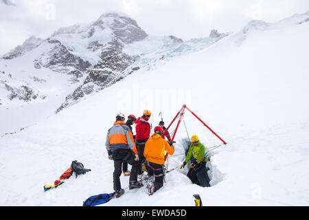 A mountain rescue technician is descending into a crevasse. When a skier breaks through the snow and tumbles down - Stock Photo