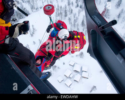 An emergency doctor and patient are being hoisted up to the rescue helicopter after a mountain accident. - Stock Photo