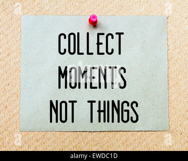 Collect Moments Not Things  written on paper note pinned with red thumbtack on wooden board. Motivation conceptual - Stock Photo