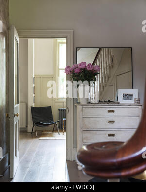 Simple square mirror on a white painted antique French chest in entrance hall - Stock Photo