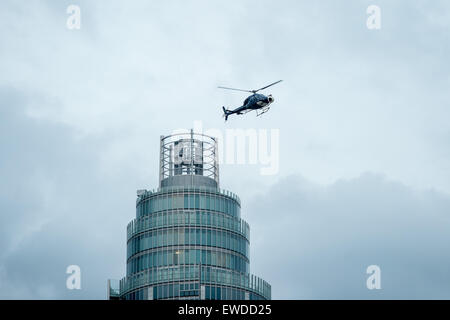 London, UK.  22 June, 2015. A helicopter flies over the MI6 building during filming of the new James Bond movie - Stock Photo