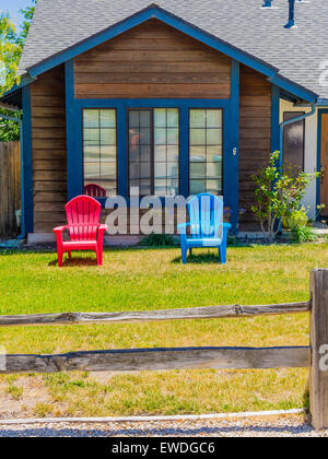 Two brightly colored lawn chairs, one red and the other blue, stand on the front lawn of a wooden house. - Stock Photo