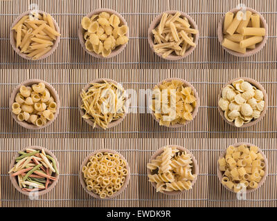 typical Italian dish various types of raw pasta in a wooden bowl - Stock Photo