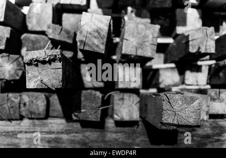Closeup of piled up construction lumber in black and white with shadows - Stock Photo