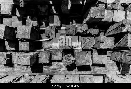 Piled up construction lumber in black and white with shadows - Stock Photo