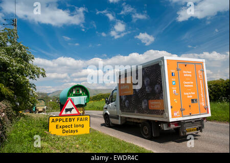 Signs warning of slow traffic on road to Appleby Horse Fair 2015, with horse drawn caravans passing by. - Stock Photo