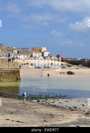 St Ives, Cornwall, England, UK.  Holidaymakers at the harbour waterfront at low tide - Stock Photo