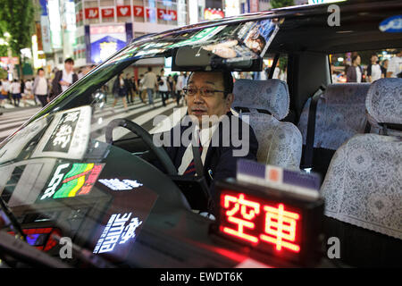 A taxi driver inside his car at night in Shinjuku, Tokyo, Japan - Stock Photo