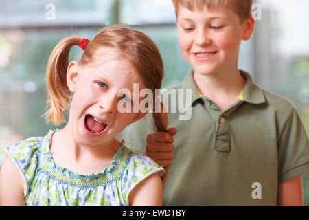 Boy Bullying Girl By Pulling Hair - Stock Photo