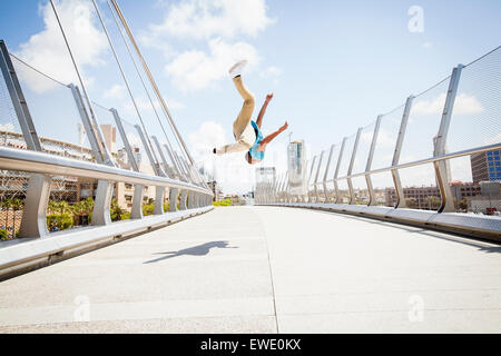 Young man somersaulting on street parcour parkour - Stock Photo