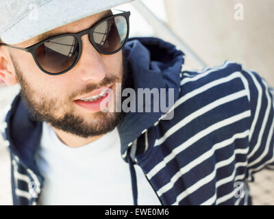 Portrait of a smiling young man wearing sunglasses - Stock Photo