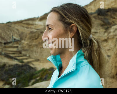 A smiling young woman, side profile, in a blue running top - Stock Photo