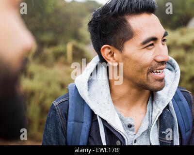 Two men, one smiling wearing a hooded top - Stock Photo
