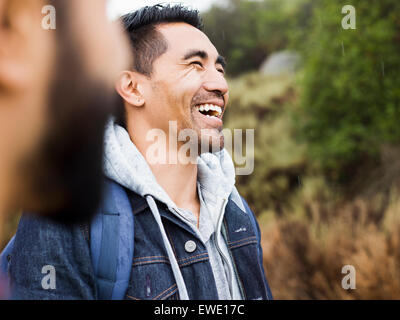 Two men, one laughing with his head back - Stock Photo