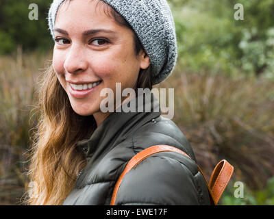 Portrait of a smiling young woman in a park - Stock Photo