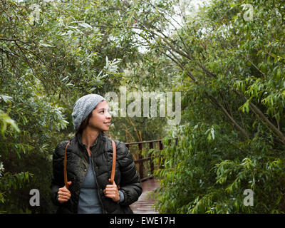 Smiling young woman walking through woodland in a park - Stock Photo
