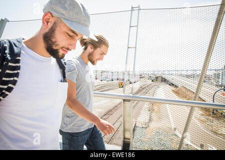 Two young men walking along a footbridge city life - Stock Photo