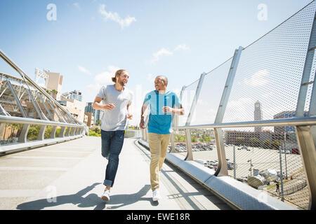 Two young men jogging along footbridge - Stock Photo