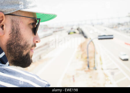 Close up of a bearded young man wearing sunglasses and a baseball cap - Stock Photo