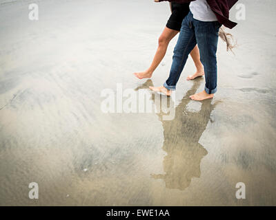 Young man and young woman walking on a beach - Stock Photo