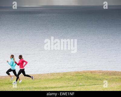 Two women jogging along the coast - Stock Photo