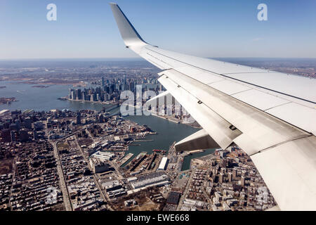New York City NY NYC Manhattan Brooklyn aerial American Airlines commercial airliner plane flight window seat view - Stock Photo