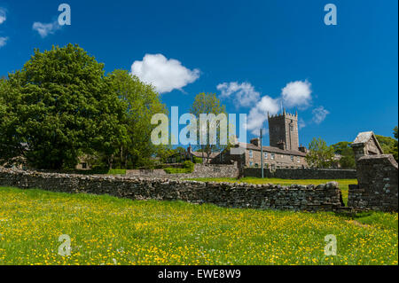St Oswalds Church, Askrigg in Wensleydale, seen over a wildflower meadow in early summer. Yorkshire, UK. - Stock Photo
