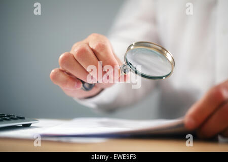 Businessman with magnifying glass reading documents - Stock Photo