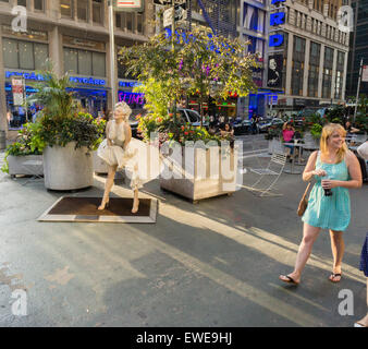 People pass Forever Marilyn by the artist Seward Johnson on the Broadway pedestrian plazas in the Garment District - Stock Photo