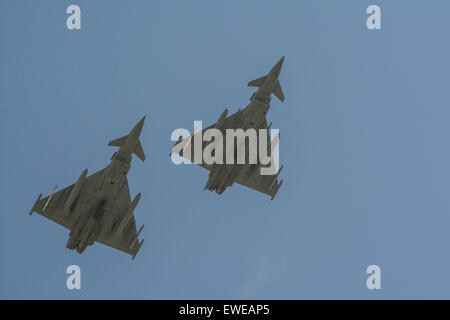 Bottom view of two RAF Typhoon fighter jets as they fly overhead against a blue sky - Stock Photo