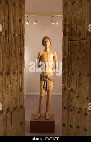 A 14th century wooden statue from Saint Sebastian and wooden doors from Northern Spain at the stand of De Backker - Stock Photo