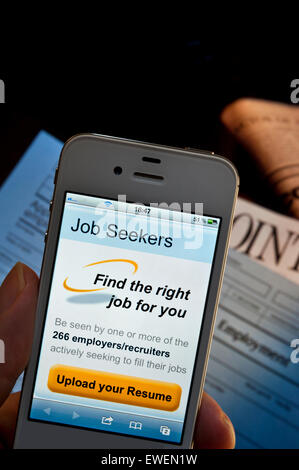 Hand holding iPhone with job seekers CV upload screen app, employment forms and newspaper appointments pages on - Stock Photo