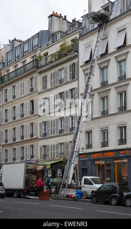 Moving truck and elevated lift for moving personal possessions to and from a 6th floor apartment in Paris, France - Stock Photo