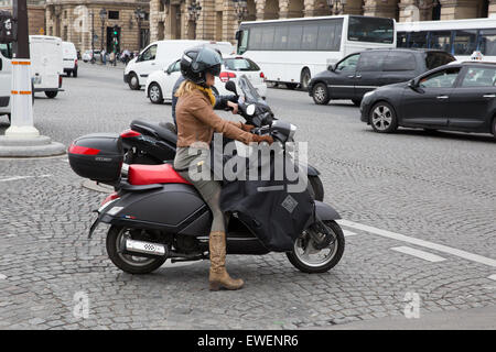 Woman riding a motorcycle wearing cowboy boots and a protective apron in Paris, France - Stock Photo