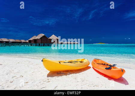 Yellow and orangel kayaks on the tropical beach with vilas in background - Stock Photo