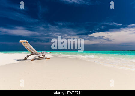 Tropical beach view of amazing water and empty chair on sand for relaxing vacations - Stock Photo