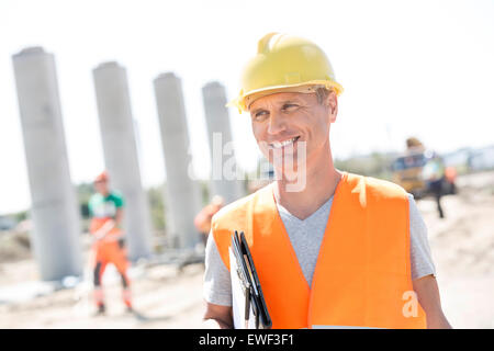 Happy architect looking away while holding clipboard at construction site - Stock Photo