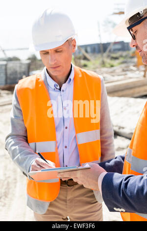 Engineers writing on clipboard at construction site - Stock Photo