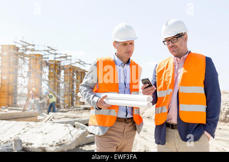 Male engineers using mobile phone at construction site against clear sky - Stock Photo