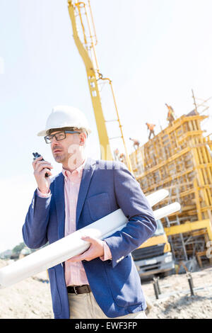 Supervisor using walkie-talkie while holding blueprints at construction site - Stock Photo