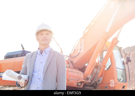 Thoughtful engineer looking away while holding blueprints by bulldozer at construction site - Stock Photo