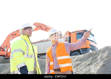 Engineer showing something to colleague while discussing at construction site against clear sky - Stock Photo