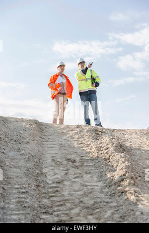 Low angle view of architect showing something to colleague at construction site against sky - Stock Photo