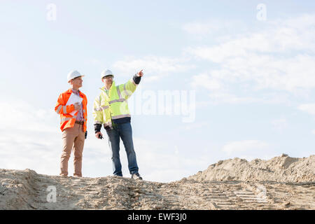 Low angle view of supervisor showing something to colleague at construction site - Stock Photo
