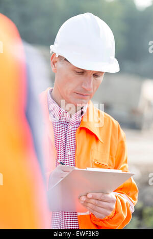 Supervisor writing on clipboard at construction site - Stock Photo