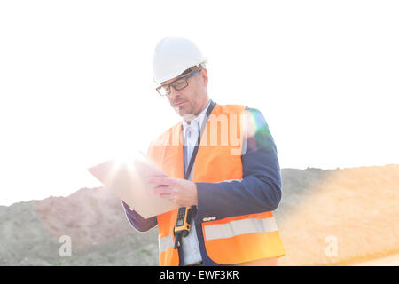 Male supervisor reading clipboard at construction site on sunny day - Stock Photo