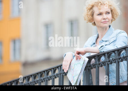 Thoughtful middle-aged woman holding map while leaning on railing - Stock Photo